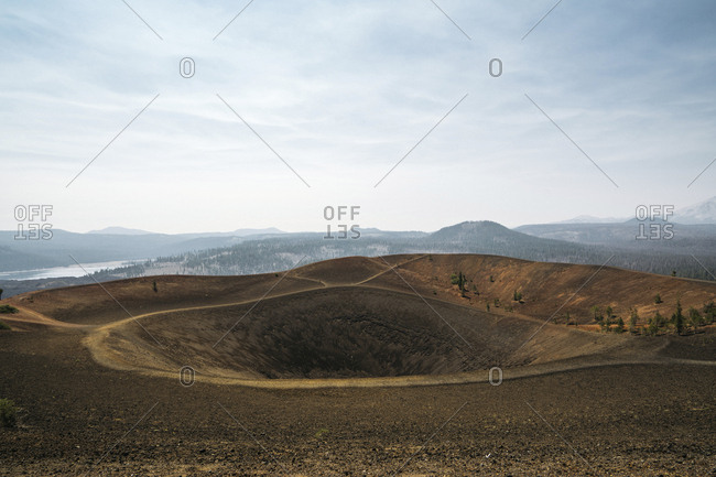 Scenic view of volcanic landscape against cloudy sky during sunny day