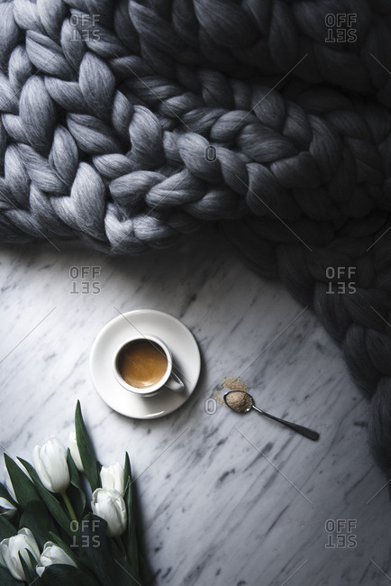 Overhead view of coffee cup by braided blanket and tulips on table