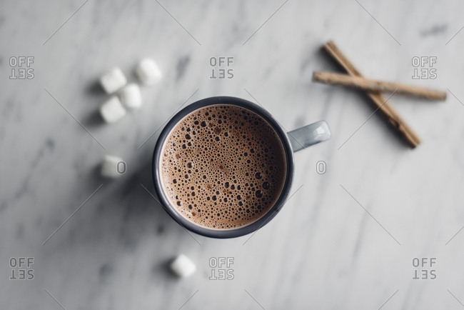 Overhead view of frothy hot chocolate in mug with marshmallows and cinnamon on table