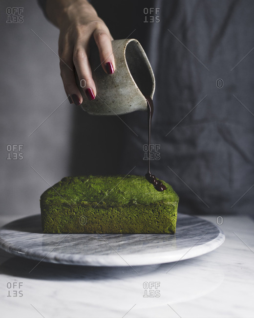 Midsection of woman pouring chocolate on matcha pound cake