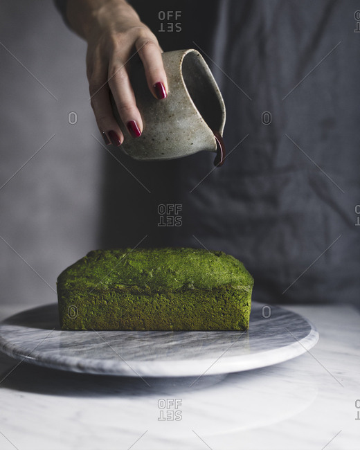 Midsection of woman pouring chocolate sauce on matcha pound cake at table
