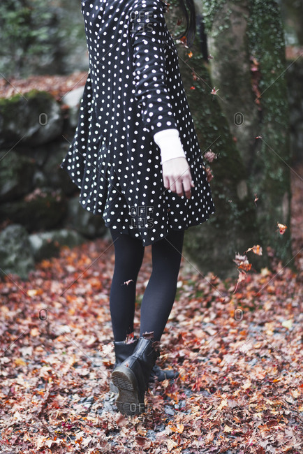Low section of woman walking on footpath during autumn in forest