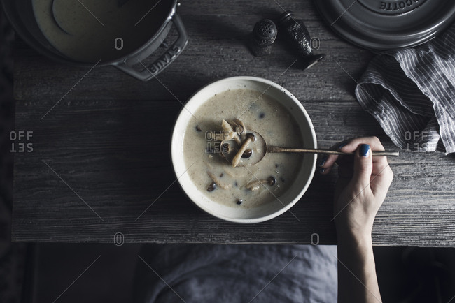 Overhead view of woman having shimeji mushroom soup at wooden table