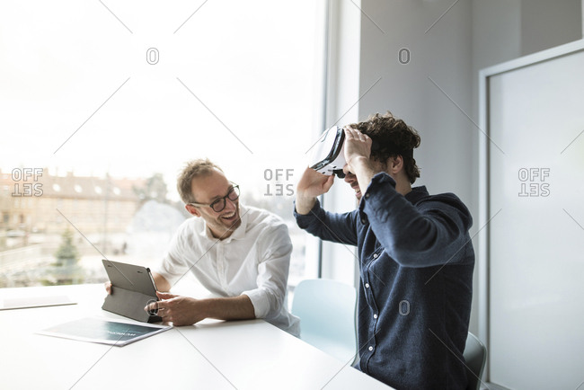 Smiling engineer looking at colleague examining virtual reality simulator in office