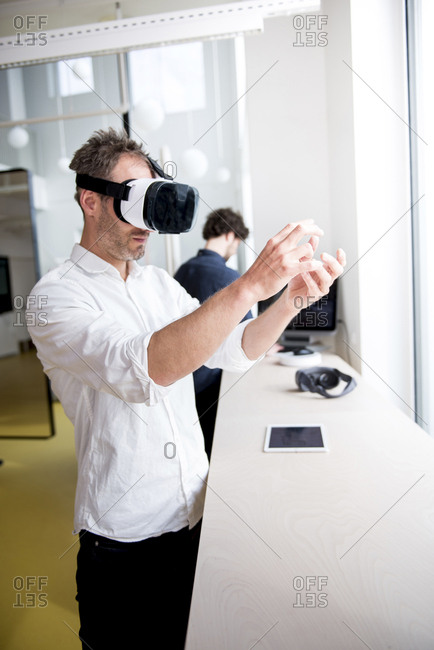 Engineer examining virtual reality simulator while coworker using computer at table