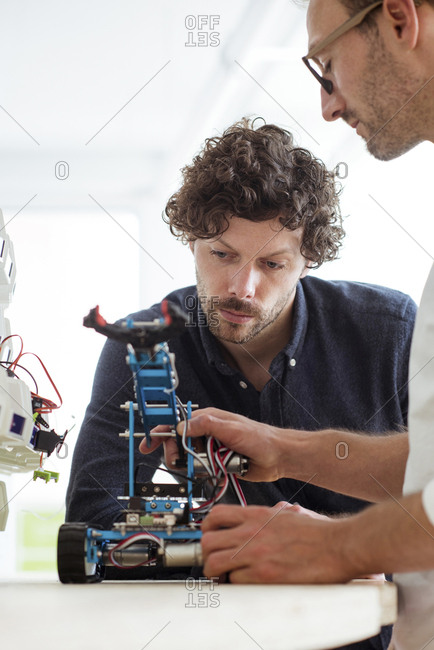 Technicians examining drone in office