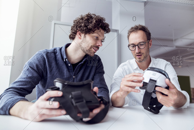 Technicians examining virtual reality simulators while sitting at table in office