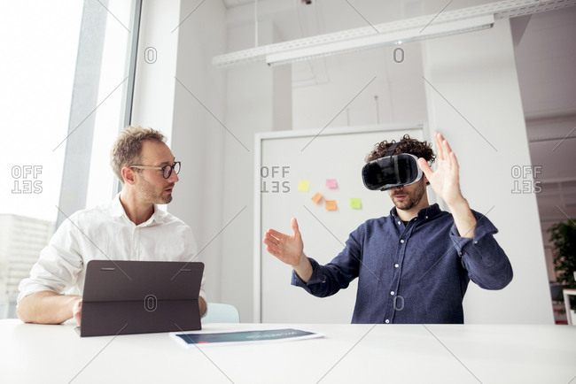Engineer with tablet computer looking at coworker examining virtual reality simulator in office