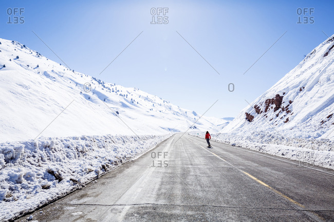 Mid Distance View Of Hiker Skating On Road By Snow Covered