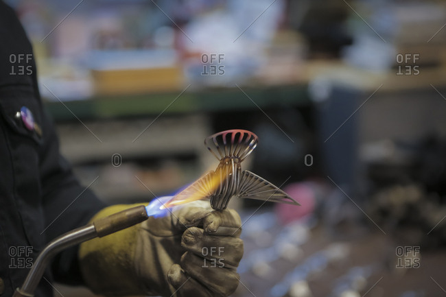 Cropped hand of engineer soldering equipment with propane torch in factory