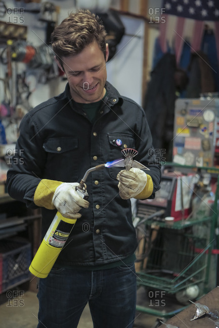Worker soldering equipment with propane torch in factory