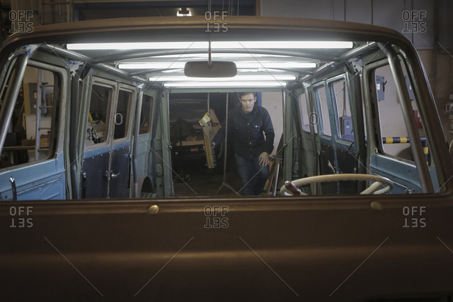 Engineer examining van in automobile factory seen through windshield