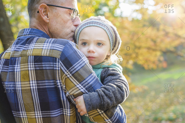 Thoughtful girl looking away while being carried by grandfather in park