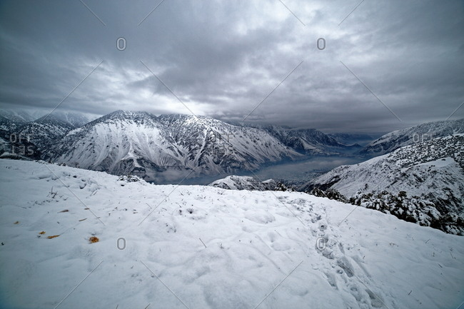 Trekkers' footprints to a ridge in the snowy mountains of Pakistan