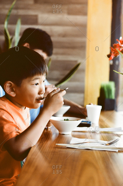 Boy eating bowl of soup at counter in restaurant window