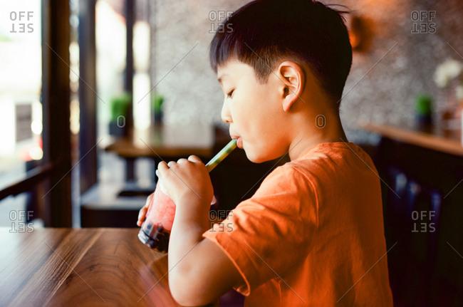 Boy drinking bubble tea in restaurant