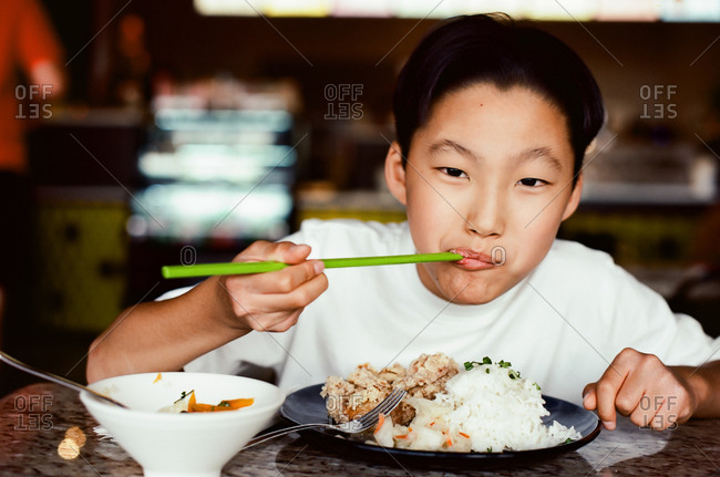 Adolescent boy eating asian food with chopsticks