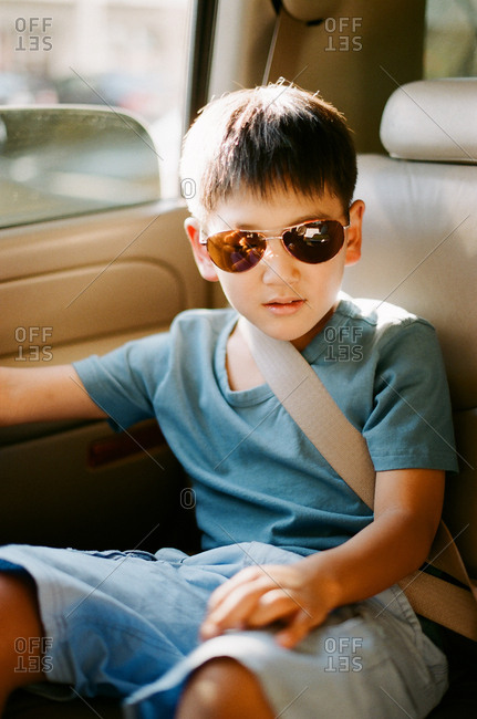 Young boy in sunglasses wearing seat belt in back seat