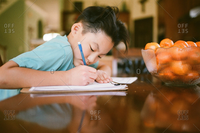 Boy doing homework at table with bowl of clementines