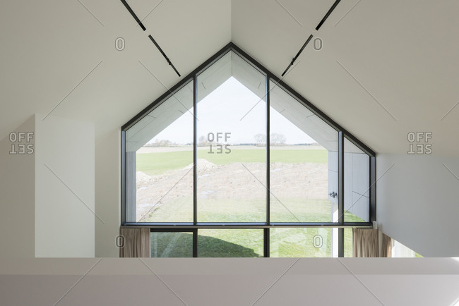 Interior vaulted ceiling with large windows overlooking countryside in modern home