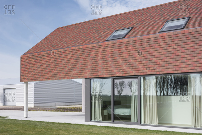 Red roof of modern home with skylights and glass walls reflecting the farmland