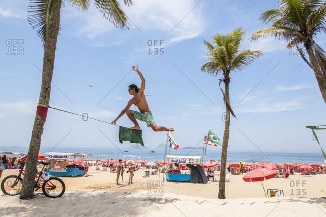 Rio de Janeiro, Brazil - December 2, 2012: Man balancing on tightrope during a lively day at Ipanema beach