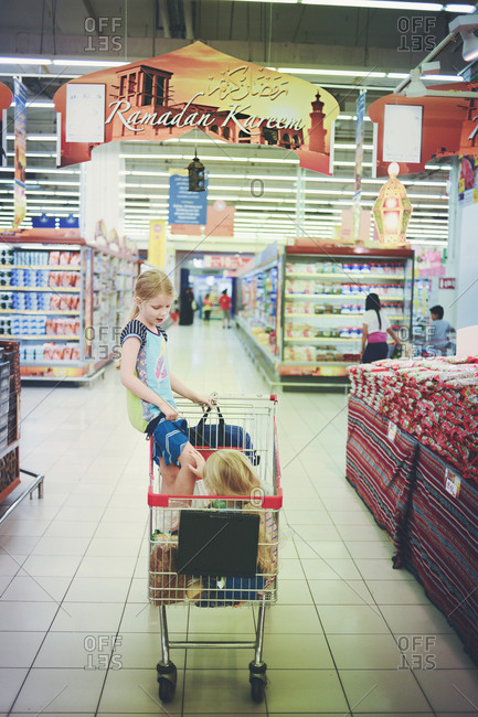 Abu Dhabi, United Arab Emirates - July 8, 2013: Girls in a shopping cart at a grocery store during Ramadan in Abu Dhabi