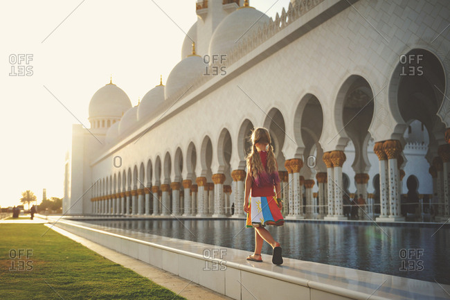 Abu Dhabi, United Arab Emirates - March 5, 2016: Girl walking by pond at the Sheikh Zayed Mosque in Abu Dhabi
