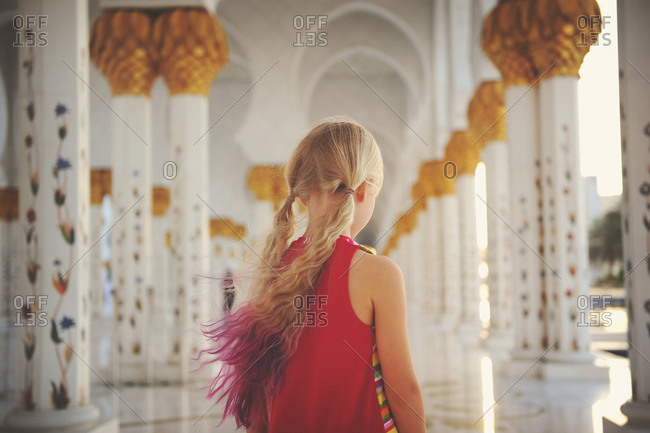Abu Dhabi, United Arab Emirates - March 5, 2016: Rear view of a girl walking in corridor of Sheikh Zayed Mosque Abu Dhabi