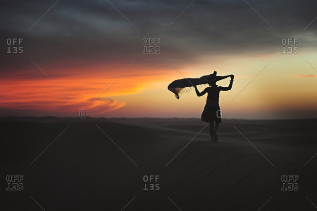 Silhouette of girl playing with a scarf in the desert at sunset in the United Arab Emirates