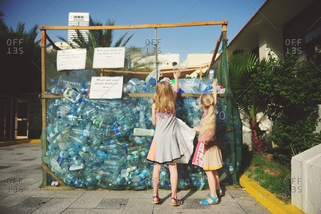 United Arab Emirates - May 15, 2014: Two girls recycling plastic bottles