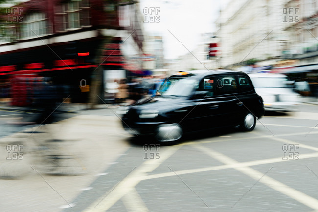 Famous black cab turning down the street, blurred motion