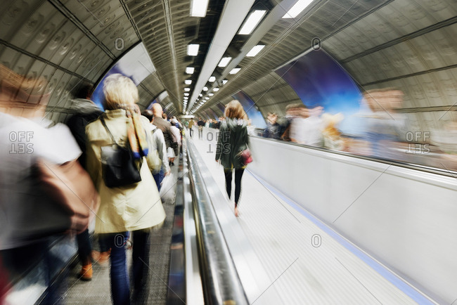Passengers walking down the travelator in London underground, blurred motion