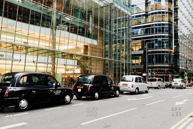 London, England - September 4, 2015: Line of famous London taxicabs standing on road at traffic light in financial district of metropolis