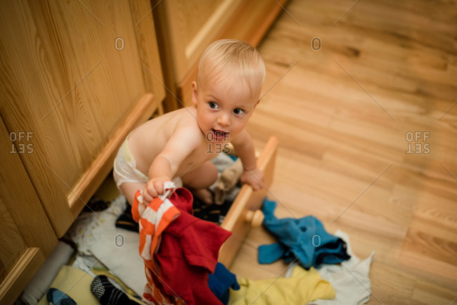 Baby boy playing inside a drawer under wooden cupboard at home