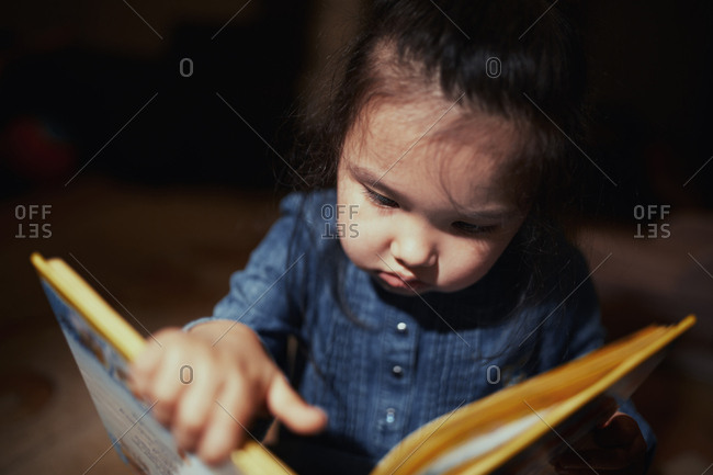 Cute 4-5 years girl reading book at home