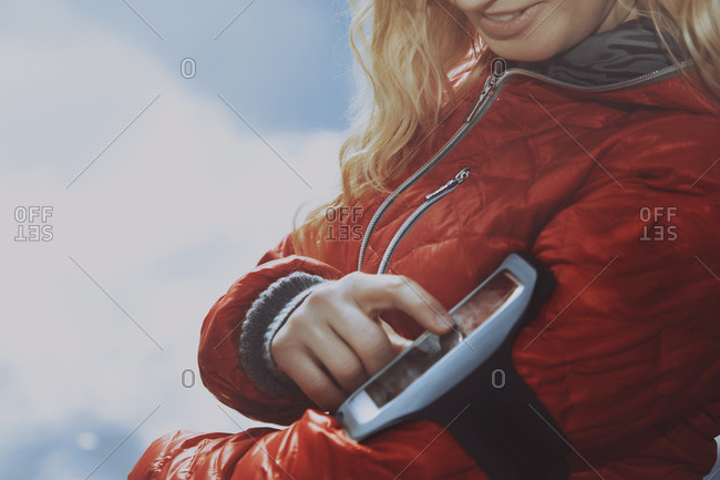 Woman jogging and wearing smartphone armband
