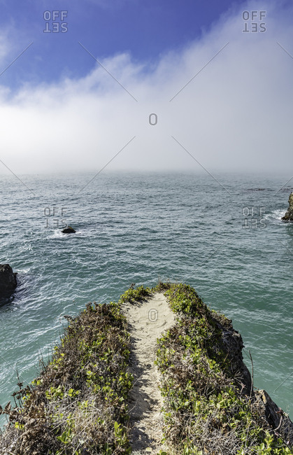 A path ends at a cliff overhanging the Pacific ocean in Mendocino, California.
