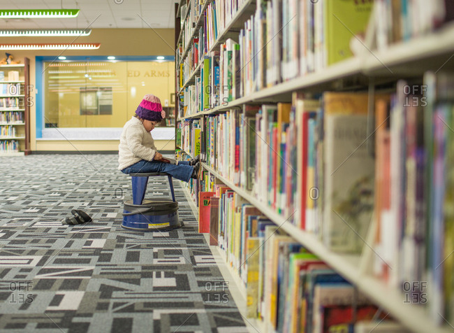 Girl reading book by library shelf