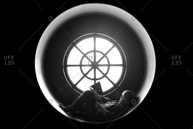 Boy in round window drawing
