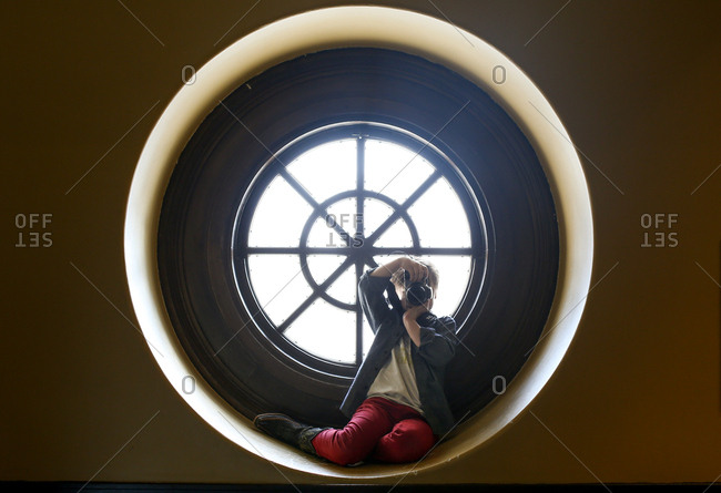 Boy in round window with camera