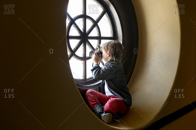 Boy in round window with a camera