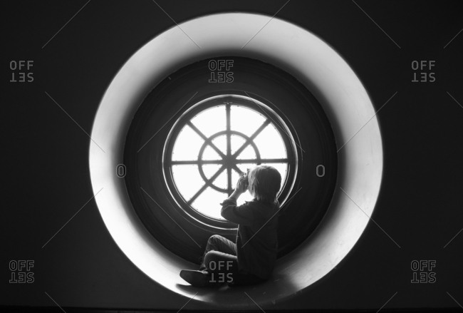 Boy taking photo in round window