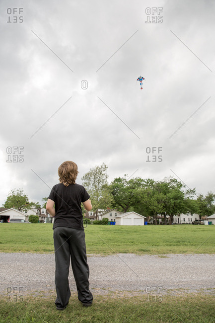 Boy flying a kite in field
