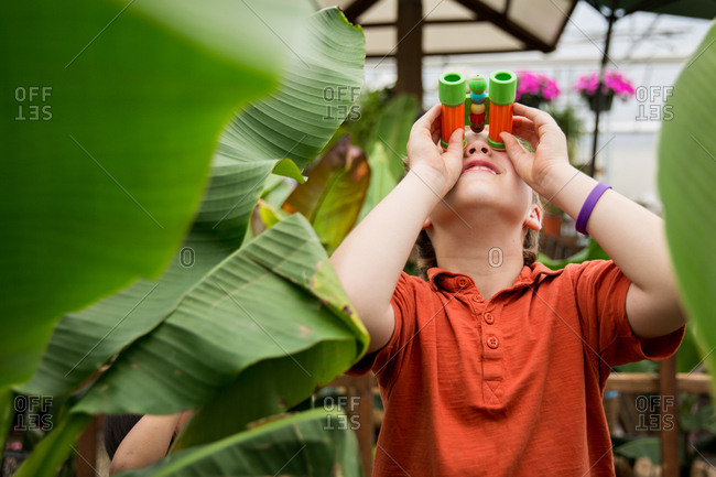 Boy using binoculars in plant nursery