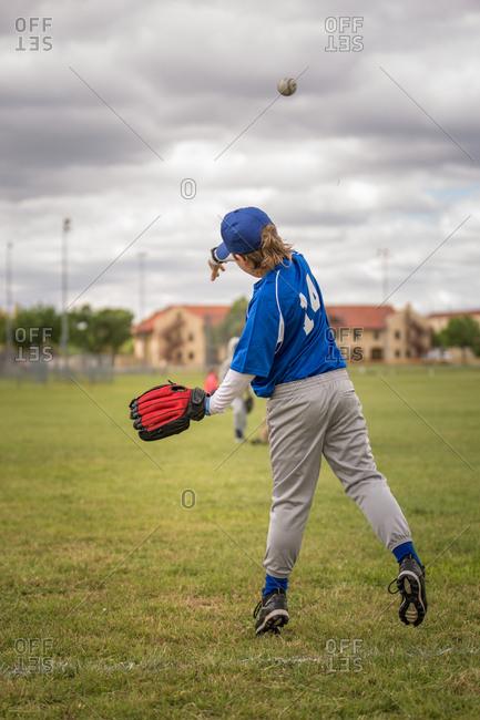 Boy in uniform throwing baseball