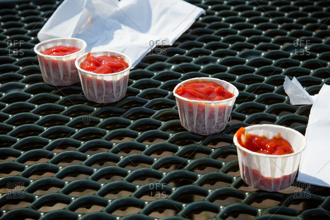 Small containers of ketchup with napkins on outdoor table
