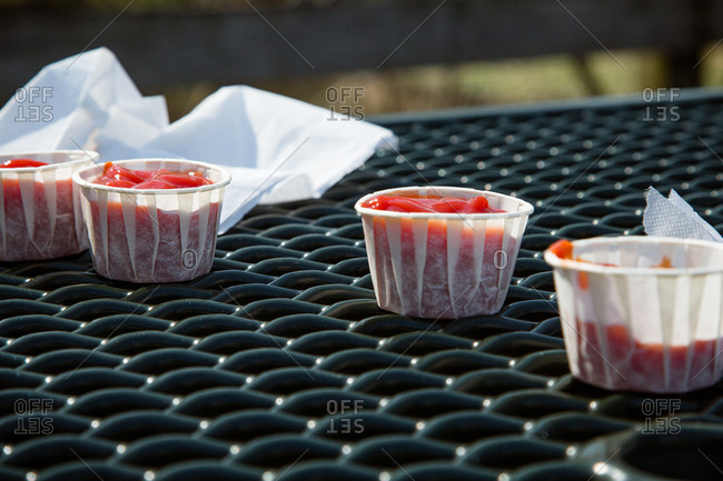 Small containers of ketchup with napkins on picnic table