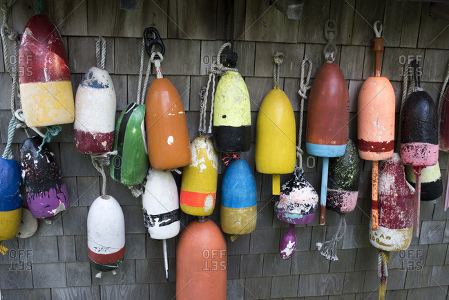 Variety of colorful fishing buoys hanging outside of cedar sided building in Cushing, Maine
