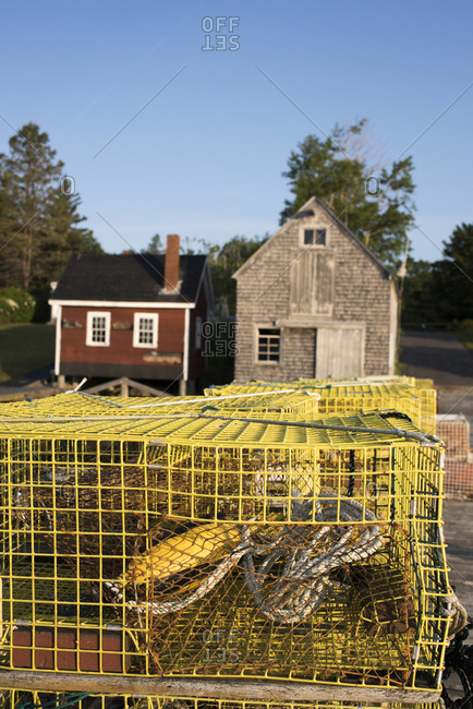 Empty lobster traps outside of buildings in Cushing, Maine